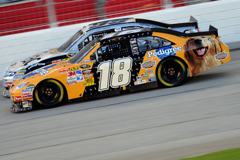 HAMPTON, GA - SEPTEMBER 05:  Kyle Busch, driver of the #18 Pedigree Toyota, races Carl Edwards, driver of the #99 Aflac Ford, during the NASCAR Sprint Cup Series Emory Healthcare 500 at Atlanta Motor Speedway on September 5, 2010 in Hampton, Georgia.  (Ph
