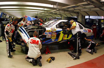 HAMPTON, GA - SEPTEMBER 05:  Greg Biffle, driver of the #16 3M Scotch Blue Ford, talks to a NASCAR official as crew members work on his car in the garage after an incident in the NASCAR Sprint Cup Series Emory Healthcare 500 at Atlanta Motor Speedway on S