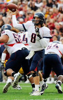 LOS ANGELES, CA - DECEMBER 05:  Quarterback Nick Foles #8 of the Arizona Wildcats completes a pass against the USC Trojans during the first quarter of the NCAA college football game at the Los Angeles Coliseum on December 5, 2009 in Los Angeles, Californi