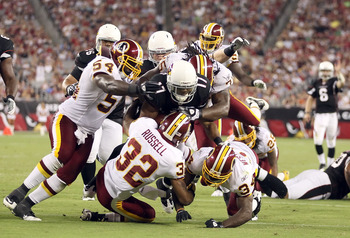 GLENDALE, AZ - SEPTEMBER 02:  Wide receiver Onrea Jones #17 of the Arizona Cardinals is tackled by H.B. Blades #54, Anderson Russell #32 and Byron Westbrook #34  of the Washington Redskins after a 16 yard reception during the second quarter of the preseas