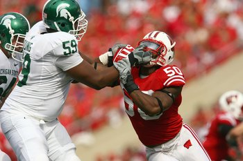 MADISON, WI - SEPTEMBER 26: O'Brien Schofield #50 of the Wisconsin Badgers gets a facemask from D.J. Young #59 of the Michigan State Spartans on September 26, 2009 at Camp Randall Stadium in Madison, Wisconsin. Wisconsin defeated Michigan State 38-30. (Ph