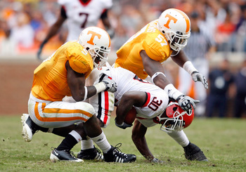 KNOXVILLE, TN - OCTOBER 10: Rico McCoy #5 and Gerald Williams #57 of the Tennessee Volunteers tackle Carlton Thomas #30 of the Georgia Bulldogs during the SEC game at Neyland Stadium on October 10, 2009 in Knoxville, Tennessee. (Photo by Andy Lyons/Getty