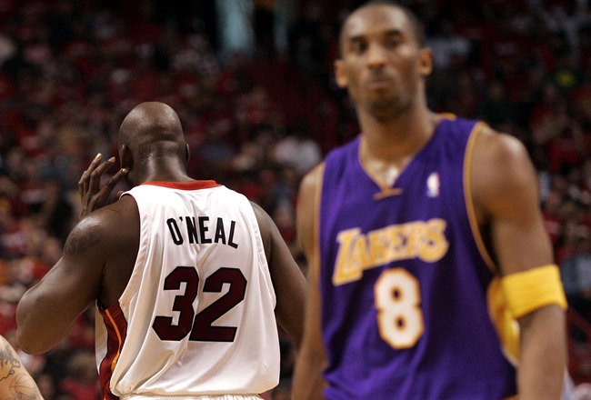 MIAMI - DECEMBER 25:  Center Shaquille O'Neal #32 of the Miami Heat keeps his back to guard Kobe Bryant #8 of the Los Angeles Lakers on December 25, 2005 at the American Airlines Arena in Miami, Florida.  NOTE TO USER: User expressly acknowledges and agre