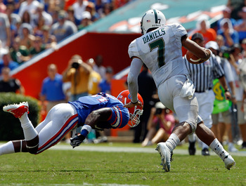 GAINESVILLE, FL - SEPTEMBER 11:  Brandon Hicks #40 of the Florida Gators attempts to tackle B.J. Daniels #7 of the South Florida Bulls during a game at Ben Hill Griffin Stadium on September 11, 2010 in Gainesville, Florida.  (Photo by Sam Greenwood/Getty