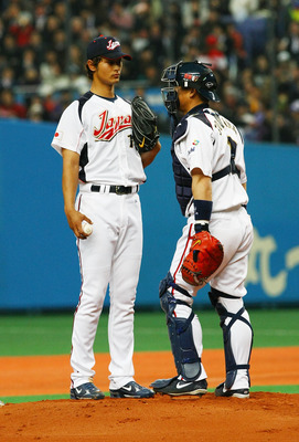 OSAKA, JAPAN - FEBRUARY 24:  Starting Pictcher Yu Darvish #11 and Chatcher Kenji Jojima #2 of Japan talk during an exhibition match between Japan and Australia at Kyocera Dome Osaka on February 24, 2009 in Osaka, Japan.  (Photo by Junko Kimura/Getty Image