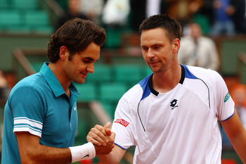PARIS - JUNE 01:  Roger Federer of Switzerland shakes hands with Robin Soderling of Sweden after the men's singles quarter final match between Robin Soderling of Sweden and Roger Federer of Switzerland at the French Open on day ten of the French Open at R