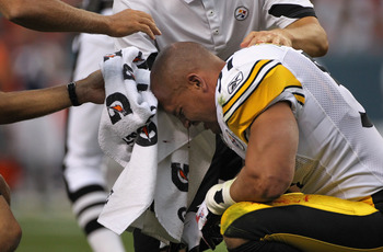 DENVER - AUGUST 29:  Linebacker James Farrior #51 of the Pittsburgh Steelers is attended to after loosing his helmet and bleeding from an injury on the play in the first quarter against the Denver Broncos during preseason NFL action at INVESCO Field at Mi