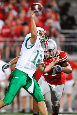COLUMBUS, OH - SEPTEMBER 2: Quarterback Brian Anderson #12 of the Marshall Thundering Herd passes as Cameron Heyward #97 of the Ohio State Buckeyes closes in at Ohio Stadium on September 2, 2010 in Columbus, Ohio. (Photo by Jamie Sabau/Getty Images)