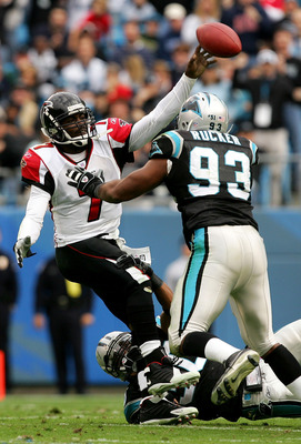 CHARLOTTE, NC - DECEMBER 4:  Michael Vick #7 of the Atlanta Falcons is sacked by Michael Rucker #93 and Mike Minter #30 of the Carolina Panthers on December 4, 2005 at Bank of America Stadium in Charlotte, North Carolina.  (Photo by Streeter Lecka/Getty I