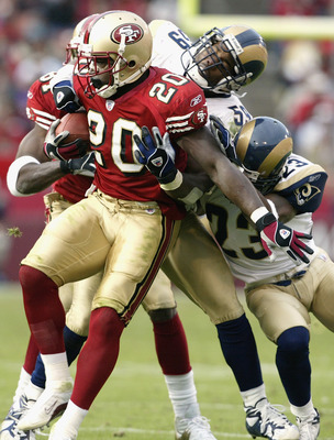 SAN FRANCISCO - NOVEMBER 2:  Running back Garrison Hearst #20 of the San Francisco 49ers is tackled by linebacker Jamie Duncan #59 and cornerback Jerametrius Butler #23 of the St. Louis Rams during the game at Candlestick Park on November 2, 2003 in San F