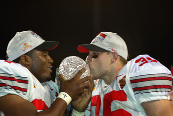 TEMPE, AZ - JANUARY 3:  Kenny Peterson #97 (l) and Matt Wilheim #35 of the Ohio State Buckeyes celebrate with the National Championship trophy after defeating the Miami Hurricanes 31-24 in double overtime the Tostitos Fiesta Bowl on January 3, 2003 at Sun