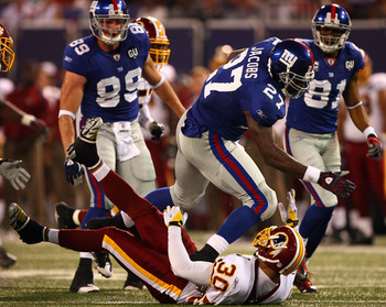 EAST RUTHERFORD, NJ - SEPTEMBER 04:  Brandon Jacobs #27 of the New York Giants runs through the tackle of LaRon Landry #30 of the Washington Redskins at Giants Stadium on September 4, 2008 in East Rutherford, New Jersey  (Photo by Al Bello/Getty Images)