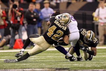 NEW ORLEANS - JANUARY 24:  Darren Sharper #42 and Jabari Greer #32 of the New Orleans Saints tackle  Sidney Rice #18 of the Minnesota Vikings during the NFC Championship Game at the Louisiana Superdome on January 24, 2010 in New Orleans, Louisiana. The Sa
