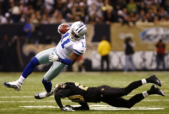 NEW ORLEANS - DECEMBER 19:  Wide receiver Roy E. Williams #11 of the Dallas Cowboys is hit by cornerback Randall Gay #20 of the New Orleans Saints at the Louisiana Superdome on December 19, 2009 in New Orleans, Louisiana. (Photo by Scott Halleran/Getty Im