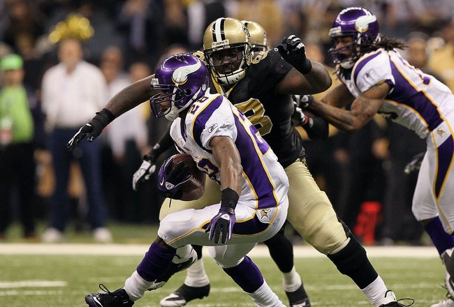 NEW ORLEANS - JANUARY 24:  Adrian Peterson #28 of the Minnesota Vikings runs the ball against Sedrick Ellis #98 of the New Orleans Saints during the NFC Championship Game at the Louisiana Superdome on January 24, 2010 in New Orleans, Louisiana. The Saints