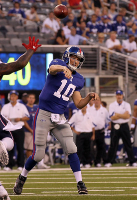 EAST RUTHERFORD, NJ - SEPTEMBER 02:  Eli Manning #10 of the New York Giants throws a first quarter touchdown pass against the New England Patriots to teammate Kevin Boss (not pictured) on September 2, 2010 at the New Meadowlands Stadium in East Rutherford