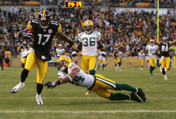 PITTSBURGH - DECEMBER 20:  Mike Wallace #17 of the Pittsburgh Steelers runs for a touchdown as Jarrett Bush #24 of the Green Bay Packers attempts to tackle in the first quarter during the game on December 20, 2009 at Heinz Field in Pittsburgh, Pennsylvani