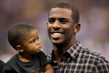 NEW ORLEANS - SEPTEMBER 09:  Chris Paul of the NBA's New Orleans Hornets holds his son Christopher as he stands on the sideline prior to the New Orleans Saints playing against the Minnesota Vikings at Louisiana Superdome on September 9, 2010 in New Orlean