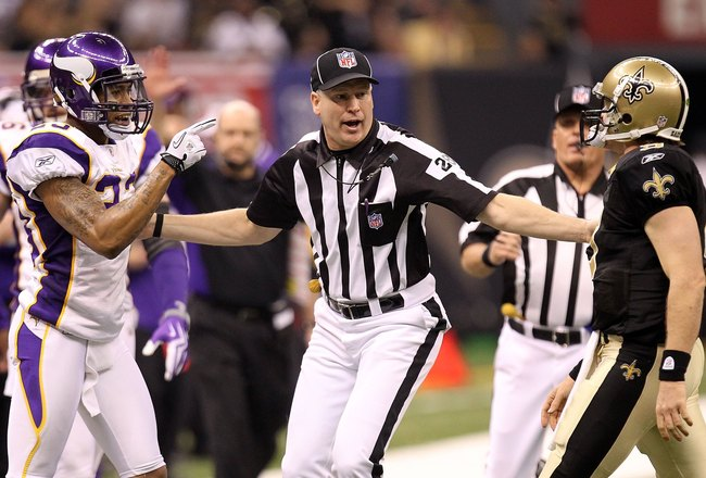 NEW ORLEANS - JANUARY 24:  Head linesman Mark Hittner seperates Drew Brees #9 of the New Orleans Saints and Cedric Griffin #23 of the Minnesota Vikings during the NFC Championship Game at the Louisana Superdome on January 24, 2010 in New Orleans, Louisian
