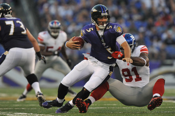 BALTIMORE - AUGUST 28:  Joe Flacco #5 of the Baltimore Ravens is sacked by Justin Tuck #91 the New York Giants at M&T Bank Stadium on August 28, 2010 in Baltimore, Maryland. The Ravens lead the Giants 17-3. (Photo by Larry French/Getty Images)