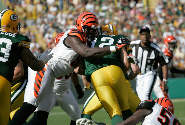 GREEN BAY, WI - SEPTEMBER 20: Quarterback Aaron Rogers #12 of the Green Bay Packers is sacked by defensive end Antwan Odem #98 of the Cincinnati Bengals at Lambeau Field on September 20, 2009 in Green Bay, Wisconsin. The Bengals defeated the Packers 31-24