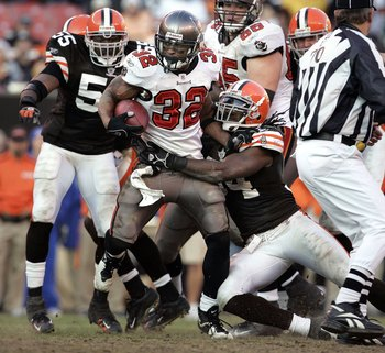 CLEVELAND, OH - DECEMBER 24:  Michael Pittman #32 of the Tampa Bay Buccaneers is tackled by Leon Williams #94 of the Cleveland Browns during the fourth quarter on December 24, 2006 at Cleveland Browns Stadium in Cleveland, Ohio.  Tampa Bay defeated Clevel