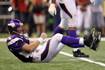 NEW ORLEANS - SEPTEMBER 09:  Quarterback Brett Favre #4 of the Minnesota Vikings grabs his torso as he lies on the turf after taking a hard hit from Roman Harper #41 of the New Orleans Saints at Louisiana Superdome on September 9, 2010 in New Orleans, Lou