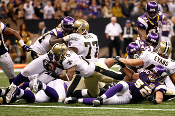 Vikings' linebacker Chad Greenway looks on as Saints' running back Pierre Thomas goes into the end-zone.