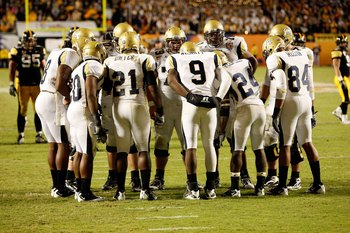 MIAMI GARDENS, FL - JANUARY 05:  Quarterback Josh Nesbitt #9 of the Georgia Tech Yellow Jackets huddles with his teammates on offense against the Iowa Hawkeyes during the FedEx Orange Bowl at Land Shark Stadium on January 5, 2010 in Miami Gardens, Florida