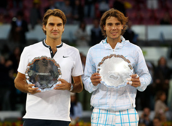 MADRID, SPAIN - MAY 16:  Mens finalist Rafael Nadal and  Roger Federer of Switzerland hold aloft their trophies after the mens final match during the Mutua Madrilena Madrid Open tennis tournament at the Caja Magica on May 16, 2010 in Madrid, Spain.  (Phot