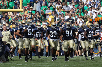 SOUTH BEND, IN - SEPTEMBER 04: Members of the Notre Dame Fighting Irish, along with coach Brian Kelly (L), run onto the field before a game against the Purdue Boilermakers at Notre Dame Stadium on September 4, 2010 in South Bend, Indiana. Notre Dame defea