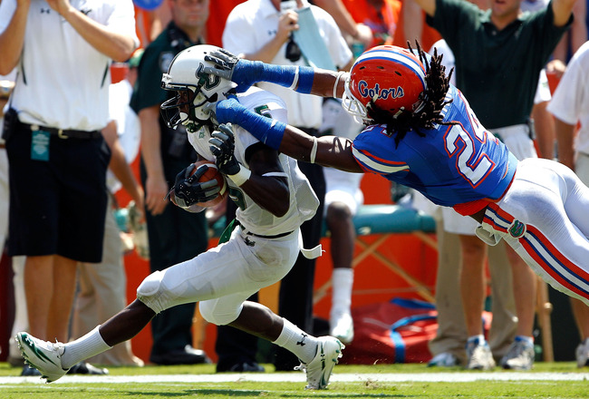 GAINESVILLE, FL - SEPTEMBER 11:   Josh Evans #24 of the Florida Gators attempts to tackle Lindsey Lamar #5 of the South Florida Bulls during a game at Ben Hill Griffin Stadium on September 11, 2010 in Gainesville, Florida.  (Photo by Sam Greenwood/Getty I