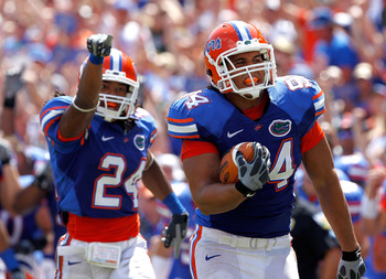 GAINESVILLE, FL - SEPTEMBER 11:   Justin Trattou #94 of the Florida Gators runs for a touchdown after making an interception during a game against the South Florida Bulls at Ben Hill Griffin Stadium on September 11, 2010 in Gainesville, Florida.  (Photo b