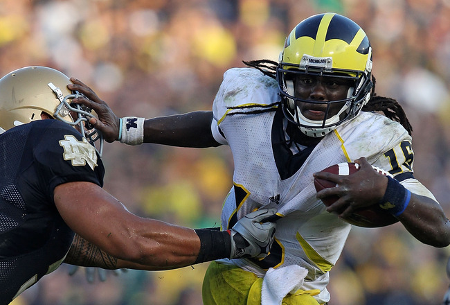 SOUTH BEND, IN - SEPTEMBER 11: Denard Robinson #16 of the Michigan Wolverines pushes off a tackle attempt by Manti Te'o #5 of the Notre Dame Fighting Irish in the final minute at Notre Dame Stadium on September 11, 2010 in South Bend, Indiana. Michigan de