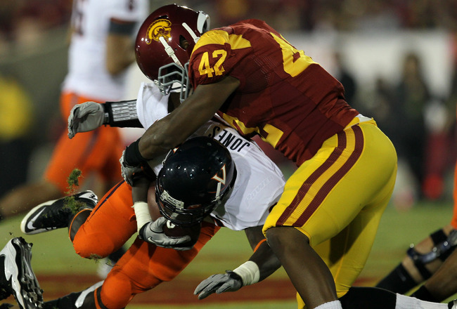LOS ANGELES - SEPTEMBER 11:  Linebacker Devon Kennard #42 of the USC Trojans tackles running back  Perry Jones #33 of the Virginia Cavaliers at Los Angeles Memorial Coliseum on September 11, 2010 in Los Angeles, California. (Photo by Stephen Dunn/Getty Im