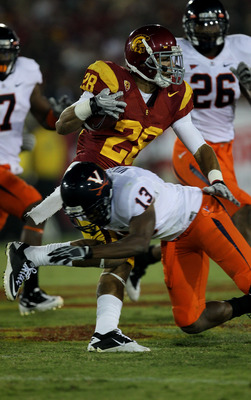 LOS ANGELES, CA - SEPTEMBER 11:  Running back Dillon Baxter #28 of the USC Trojans carries the ball against cornerback Chase Minnifield #13 of the Virginia Cavaliers at Los Angeles Memorial Coliseum on September 11, 2010 in Los Angeles, California. USC wo