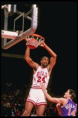 1990:  Center Bill Cartwright of the Chicago Bulls (left) slam dunks against guard Jeff Hornacek of the Phoenix Suns during a game at Chicago Stadium in Chicago, Illinois. Mandatory Credit: Jonathan Daniel  /Allsport