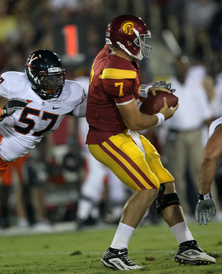 LOS ANGELES - SEPTEMBER 11:  Linebacker Darnell Carter #57 of the Virginia Cavaliers forces a fumble as he sacks quarterback Matt Barkley #7 of the USC Trojans at Los Angeles Memorial Coliseum on September 11, 2010 in Los Angeles, California. (Photo by St