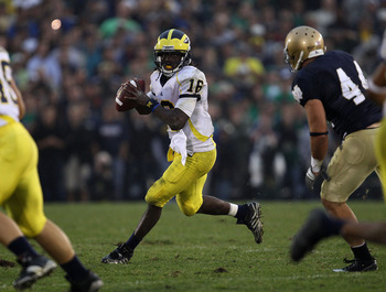 SOUTH BEND, IN - SEPTEMBER 11: Denard Robinson #16 of the Michigan Wolverines looks for a receiver under pressure from Carlo Calabrese #44 of the Notre Dame Fighting Irish at Notre Dame Stadium on September 11, 2010 in South Bend, Indiana. Michigan defeat