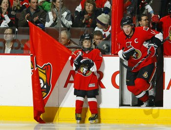 OTTAWA - DECEMBER 8:  A young boy holds an Ottawa Senators team flag as Daniel Alfredsson #11 of the Ottawa Senators take the ice before the game against the Montreal Canadiens at Scotiabank Place on December 8, 2009 in Ottawa, Ontario, Canada. The Canadi
