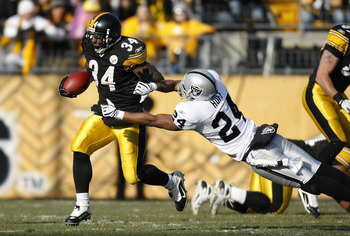 PITTSBURGH - DECEMBER 06:  Rashard Mendenhall #34 of the Pittsburgh Steelers tries to get around the tackle of Michael Huff #24 the Oakland Raiders during a first quarter run on December 6, 2009 at Heinz Field in Pittsburgh, Pennsylvania.  (Photo by Grego