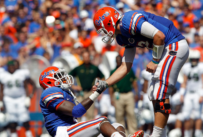 GAINESVILLE, FL - SEPTEMBER 11:  Quarterback John Brantley #12 of the Florida Gators grabs the hand of Jeffery Demps #12 during a game against the South Florida Bulls at Ben Hill Griffin Stadium on September 11, 2010 in Gainesville, Florida.  (Photo by Sa