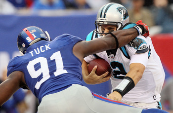 EAST RUTHERFORD, NJ - SEPTEMBER 12:  Jimmy Clausen #2 of the Carolina Panthers tries to avoid a sack attempt from Justin Tuck #91 of the New York Giants on September 12, 2010 at the New Meadowlands Stadium in East Rutherford, New Jersey. The Giants defeat
