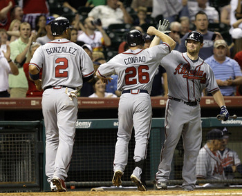 HOUSTON - AUGUST 10:  Brooks Conrad #26 of the Atlanta Braves is congratulated by Alex Gonzalez #2 after hitting a two run home run in the ninth inning against Matt Lindstrom of the Houston Astros at Minute Maid Park on August 10, 2010 in Houston, Texas.