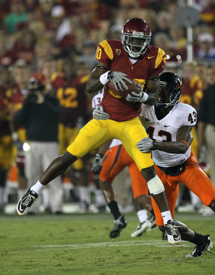 LOS ANGELES - SEPTEMBER 11:  Wide receiver Brandon Carswell #80 of the USC Trojans makes a catch in front of cornerback Mike Parker #43 of the Virginia Cavaliers at Los Angeles Memorial Coliseum on September 11, 2010 in Los Angeles, California. USC won 17