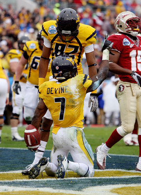 JACKSONVILLE, FL - JANUARY 01: Running back Noel Devine #7 and wide receiver Alric Arnett #82 of the West Virginia Mountaineers celebrate Devine's first quarter touchdown in the first quarter against the Florida State Seminoles during the Konica Minolta G