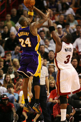 MIAMI - DECEMBER 19:  Dwyane Wade #3 of the Miami Heat guards Kobe Bryant #24 of the Los Angeles Lakers as he takes a shot at American Airlines Arena on December 19, 2008 in Miami, Florida. The Heat defeated the Lakers 89-87. NOTE TO USER: User expressly