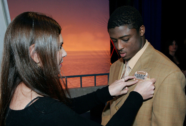 FORT LAUDERDALE, FL - DECEMBER 06:  Running back Warrick Dunn of the Atlanta Falcons gets his nametag adjusted on stage during the taping of the NFL Players Week 10th Anniversary on Wheel Of Fortune on December 6, 2005 in Fort Lauderdale, Florida. (Photo