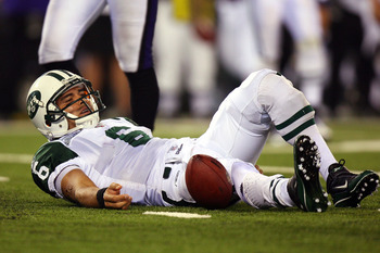 EAST RUTHERFORD, NJ - SEPTEMBER 13:  Mark Sanchez #6 of the New York Jets lays on the ground after a sack in the fourth quarter by the Baltimore Ravens during their home opener at the New Meadowlands Stadium on September 13, 2010 in East Rutherford, New J