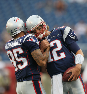 FOXBORO, MA - AUGUST 12: Aaron Hernandez  #85 and Tom Brady #12 of the New England Patriots greet each other before the the preseason game against the New Orleans Saints at Gillette Stadium on August 12, 2010 in Foxboro. Massachusetts. (Photo by Jim Rogas